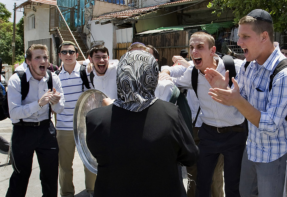 Israeli youths jeer at a Palestinian woman in Sheikh Jarra neighbourhood of Jerusalem who has just been made homeless by settlers