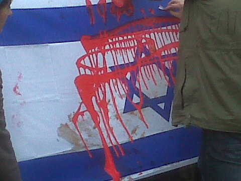 Supporters spattered an Israeli flag with fake blood.